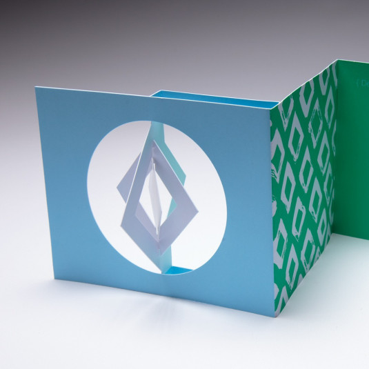 Designers use the Diamond Spinner Holiday Card to send a greeting to their clients